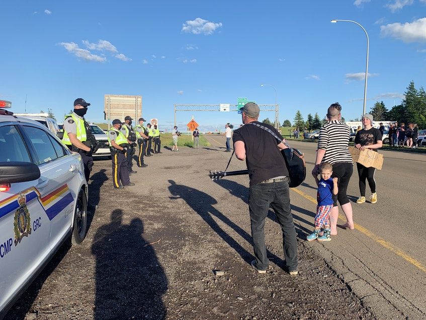 Protesters yell at RCMP assembled at the Nova Scotia-New Brunswick border in Fort Lawrence, N.S., on Wednesday night. RCMP broke up the blockade that lasted nearly 24 hours and stopped traffic coming into and leaving Nova Scotia. - Darrell Cole