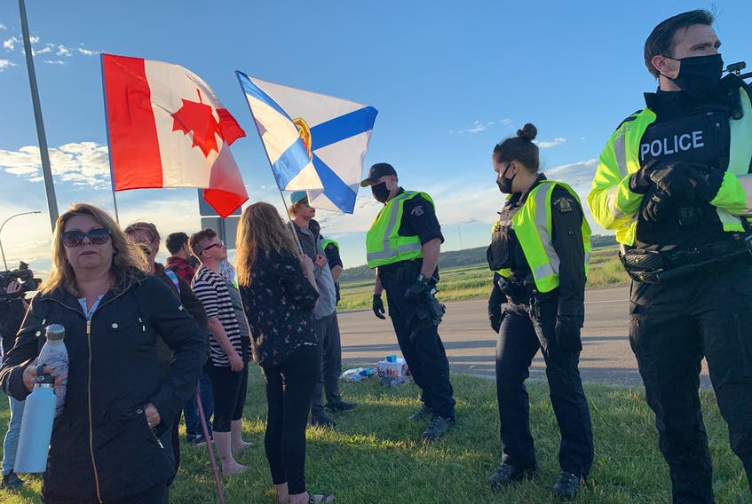RCMP officers move protesters away from Highway 104 on Wednesday evening ending a blockade at the Nova Scotia border that lasted nearly 24 hours.