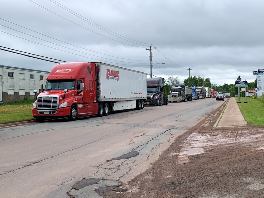 Trucks line Industrial Park Drive in Amherst on Wednesday after protesters shut down the Trans-Canada Highway at the border overnight Tuesday. Transport trucks were diverted into Amherst and soon filled mall parking lots and nearby streets. - Darrell Cole
