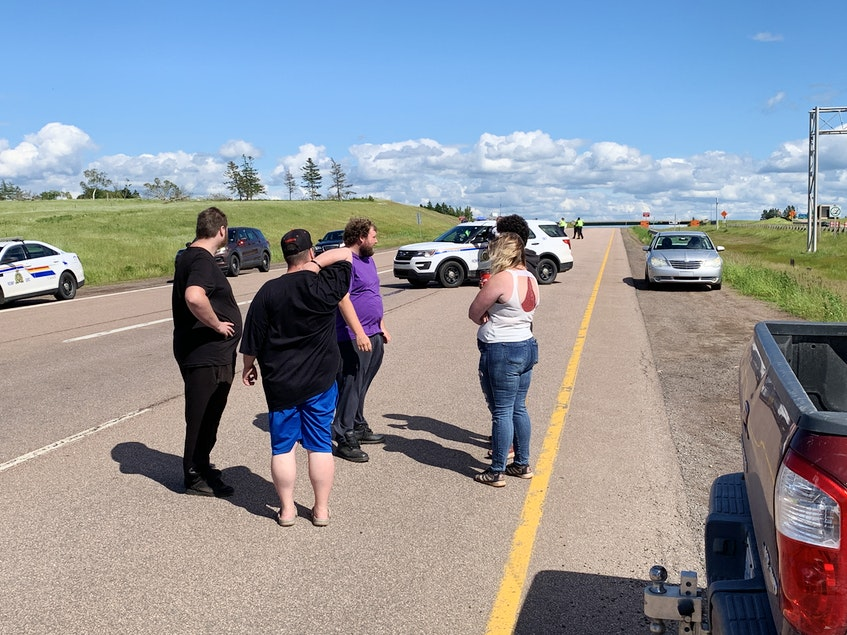 People talk on the side of the highway during a protest that blocked both lanes of the Trans-Canada Highway entering Nova Scotia at Fort Lawrence, N.S. - Darrell Cole