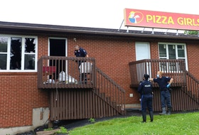 Halifax police and fire department investigators work behind the Pizza Girls restaurant on Portland Street in Dartmouth on Wednesday morning, June 23, 2021, after a fire the previous night.