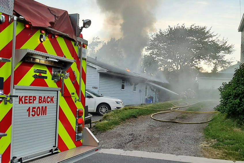 Firefighters battle a structure fire on Herbert Street in Sydney Wednesday evening. The fire is believed to have started around 8:20 p.m. The cause of the fire was unknown at press time.