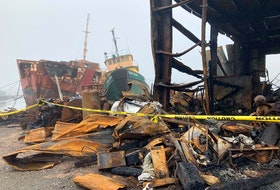 A marine services centre in Marie Joseph burned on June 15. In the background is the former CCGS Sir Charles Tupper, a navigational aids tender that the building's owner, Clem Fleet, had been dismantling.