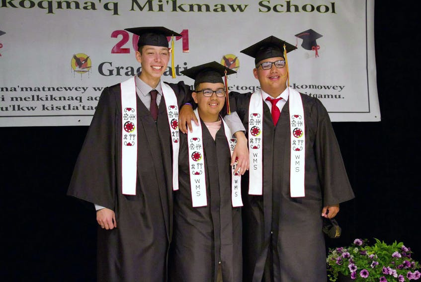 Logan Prosper, right, stands arm and arm with two of his friends at their graduation ceremony at We'koqma'q Mikmaw School on June 16. With him are, from left, Brayden Googoo and Owen Bernard. CONTRIBUTED