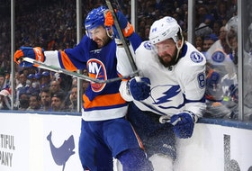 Nikita Kucherov of the Tampa Bay Lightning, being checked into the boards by Adam Pelech of the New York Islanders, is a question mark for their Game 7 showdown tonight at Amalie Arena..