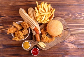 Delicious but unhealthy food with ketchup and mustard on vintage cutting board. Fast carbohydrates, junk and fast food. Warm wooden background. Getty Images/iStockphoto