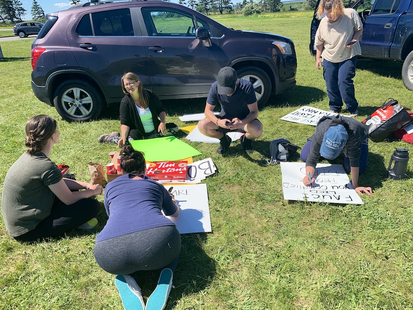 A small group of protesters make signs near the Nova Scotia-New Brunswick border in Fort Lawrence, N.S. on Thursday. RCMP reopened the Trans-Canada Highway at the border on Wednesday night. Some protesters returned to the site early Thursday, although there remains a heavy RCMP presence. - Darrell Cole