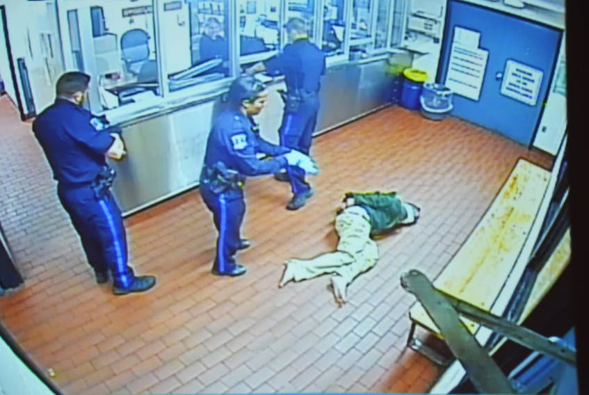 Halifax police constables Justin Murphy, Donna Lee Paris and Ryan Murphy get ready to transport Corey Rogers from the booking area to a cell on the night of June 15, 2016, in this photo taken from a police video. Rogers, who had a spit hood over his head, later died in the cell from asphyxiation. The Nova Scotia Police Review Board is hearing an appeal launched by Rogers' mother, Jeannette, regarding the internal discipline handed out to the three arresting officers.