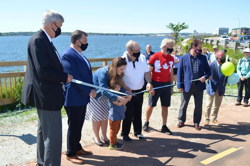 Karri Shea's son, Linden, cuts the ribbon on Thursday, June 24 to officially open the Hillsborough Bridge active transportation path. Also pictured are, from left, Stratford Mayor Steve Ogden, P.E.I. Premier Dennis King, Cardigan MP Lawrence MacAulay, Charlottetown MP Sean Casey, P.E.I. Transportation and Infrastructure Renewal Minister James Aylward and Charlottetown Mayor Philip Brown. - Dave Stewart