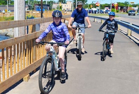 Mark Weeks, centre, goes for a bike ride on the Hillsborough Bridge active transportation path with his two children, Addison, left, 11, and Carter, 8, on June 24 in Charlottetown.