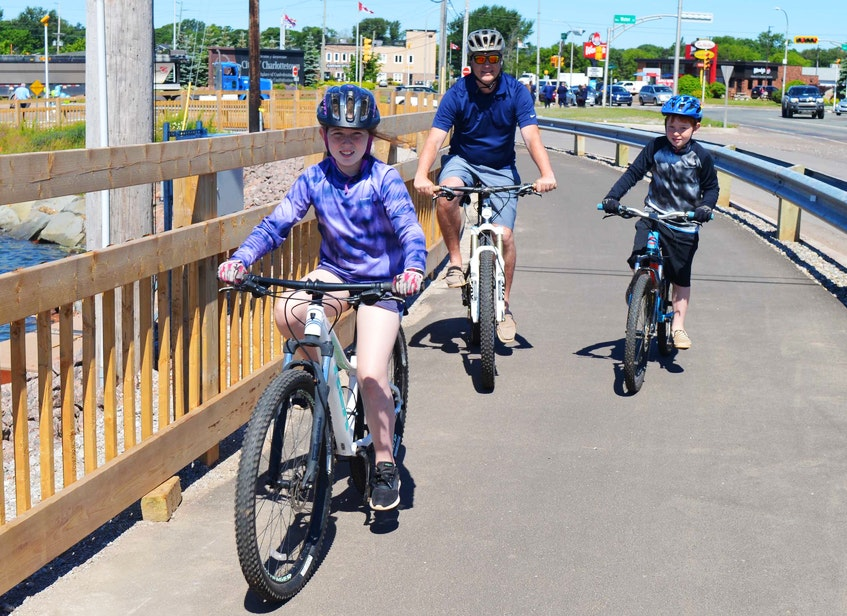 Mark Weeks, centre, goes for a bike ride on the Hillsborough Bridge active transportation path with his two children, Addison, left, 11, and Carter, 8, on June 24 in Charlottetown. - Dave Stewart • The Guardian
