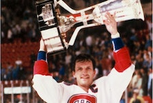 Canadiens captain Guy Carbonneau hoists the Prince of Wales Conference trophy after beating the New York Islanders in 1993 at the Forum and advancing to the Stanley Cup final.