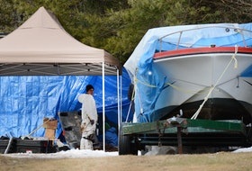 Both the medical examiner and police personnel work at an excavation in the back yard of a Shad Bay home on March 8, 2013. They were searching a property belonging to the brother of Andrew Paul Johnson, a suspect in several Nova Scotia cold case murders who was just denied parole in B.C.