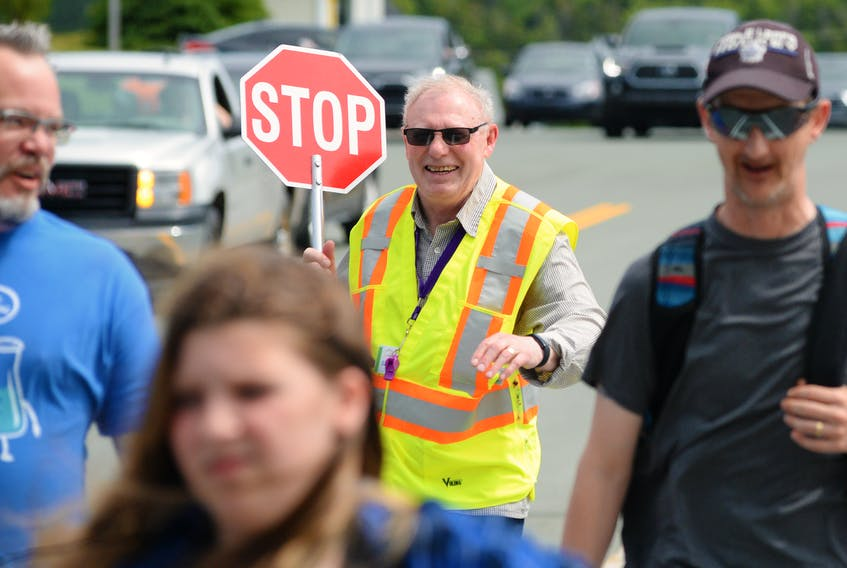 Crossing guard Edmund Hunt works one of his last shifts at the crosswalk on Topsail Road at Hazelwood Elementary.  Keith Gosse/The Telegram