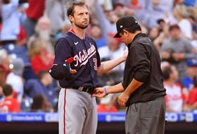 Max Scherzer of the Washington Nationals, left, allows the umpire to check his hat and belt for foreign substances. Scherzer was checked three times in four innings for substances and nothing was found. USA TODAY