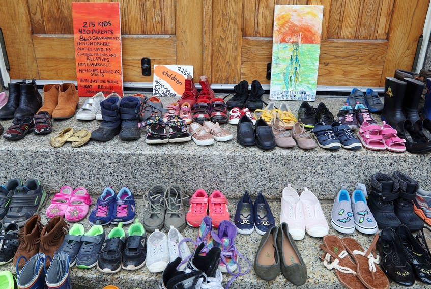 A collection of child-sized shoes are placed outside St. Mary's Basilica on Spring Garden Road. The pairs of footwear symbolize the 215 children found in a mass grave outside a former residential school in Kamloops, BC.