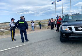 RCMP officers speak with protesters at a blockade that took place just inside the Nova Scotia border last week. Columnist Jim Vibert says provincial PC Party leader Tim Houston did the right thing by removing MLA Elizabeth Smith-McCrossin from caucus for supporting the protest against retightened travel restrictions between Nova Scotia and New Brunswick.