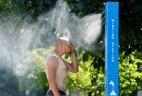 A man cools off at a misting station during the scorching weather of a heat wave in Vancouver on Sunday, June 27, 2021.