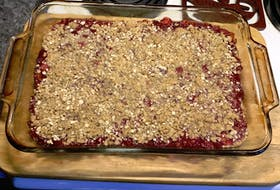 """Barbara Nash had just taken these out of the oven when she stopped to snap this photo. I'm not sure that I could have waited that long before """"sampling."""" On a day like today, I bet a scoop of ice cream would be perfect on these lovely rhubarb squares."""