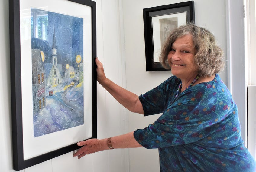 At the Fraser Art Gallery, Joy Laking hangs one of her Great Village paintings she did while spending a week at the Elizabeth Bishop House last winter with fellow artist Susan Paterson.