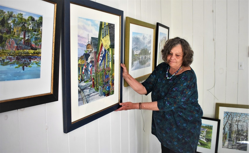 Portapique artist Joy Laking arranging three Tatamagouche paintings she did recently for her show at the Fraser Art Gallery. - Richard MacKenzie
