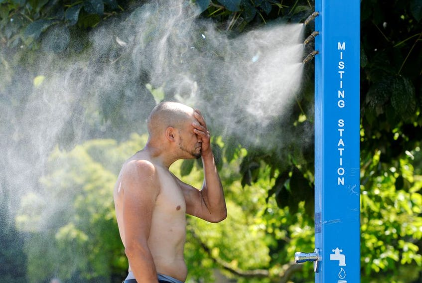 A man cools off at a misting station during the scorching weather of a heatwave in Vancouver on Sunday.