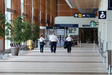Canadian Air Transport Security Authority (CATSA) employees walk down an eerily quiet hallway toward arrivals at Halifax Stanfield International Airport Tuesday afternoon. With Phase 3 of the lifting of COVID-19 restrictions the airport might be busier.