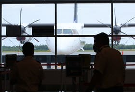 Two Canadian Air Transport Security Authority (CATSA) employees walk around a quiet pre-screening queue at Halifax Stanfield International Airport Tuesday afternoon. With Phase 3 of the lifting of COVID-19 restrictions the airport might be busier.