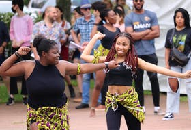 Chinwe Okwuwolu, left, and Vanessa Kuku perform as the Fela Ladies dance group at the DiverseCity Festival in Charlottetown. Member Shalom Nnadi can be seen in the background beside founding member Daniel Ohaegbu.