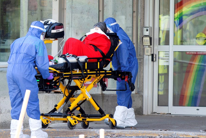 """Ambulance attendants transport a resident from a seniors' long-term care home, amid the outbreak of COVID-19 in Laval, Quebec, April 16, 2020. Quebec """"appeared to be the province that came closest to accurately and completely measuring the full magnitude of its COVID-19 fatalities,"""" a new report says."""