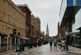 A couple of people stroll down an empty Argyle Street in Halifax.  TIM KROCHAK PHOTO
