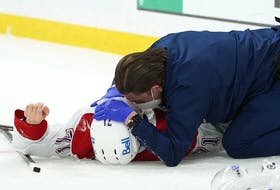 Jake Evans is tended to on the ice by Graham Rynbend, the Canadiens' head athletic therapist, after suffering a concussion as a result of a violent check from the Jets' Mark Scheifele during Game 1 of their North Division final playoff series Wednesday night in Winnipeg.