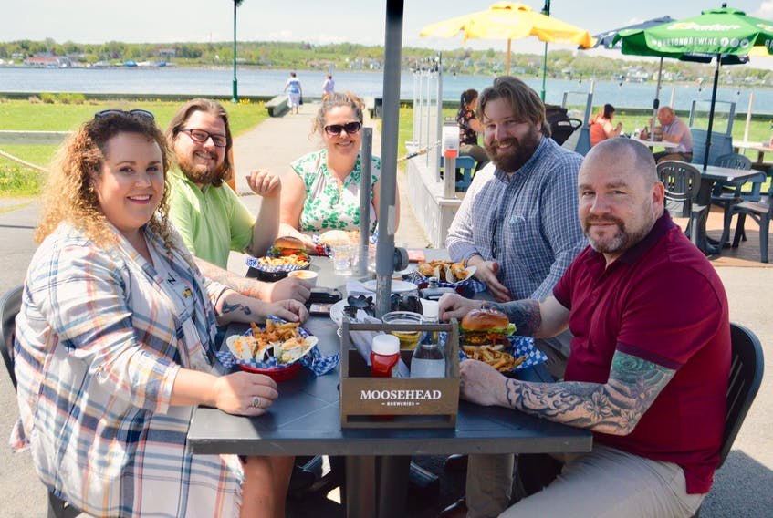 Perhaps it was the beautiful day or maybe the easing of COVID-19-related restrictions, but whatever the reason, Cape Breton residents starved for a sit-down meal have been flocking to outdoor patios and decks since they reopened on Wednesday. Above, this group of friends was found enjoying a bite of lunch on Thursday at the Portside pub on the Sydney waterfront. Clockwise from left: Courtney Richardson, Kyle Richardson, Nancy Beaton, Nick Jones and Wayne Jenkins. DAVID JALA/CAPE BRETON POST