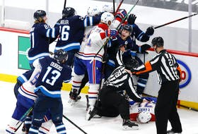 Winnipeg Jets forward Nikolaj Ehlers (27) attempts to keep players away from injured Montreal Canadiens centre Jake Evans (71) after a hit by Jets centre Mark Scheifele late in Game 1 of the second round of the 2021 Stanley Cup Playoffs at Bell MTS Place in Winnipeg on Wednesday.