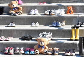 Shoes and boots of all sizes sit on the steps of St. Ambrose Cathedral in remembrance and honour of the up to 215 children found buried at a former Indian Residential School in Kamloops, BC. TINA COMEAU • TRICOUNTY VANGUARD