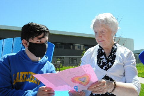 Evan Fleming, a Grade 6 student at Lakecrest Independent School in St. John's, chats with Lanes Independent and Assisted Living resident Betty Anderson after she received a personal greeting card from him on Thursday. Joe Gibbons • The Telegram