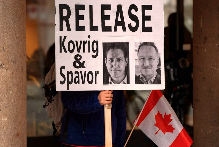 A man holds a sign calling for China to release detained Canadians Michael Kovrig and Michael Spavor, who have been held in China for more than two years.