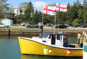 One of the moderate livelihood fishing boats heads out into the St. Peter's Canal in the fall of 2020. The boat is flying Mi'kmaq grand council flags as the driver of the boat holds up the tags issued by Potlotek First Nation. The 196 traps seized by DFO last year were returned to harvesters. CAPE BRETON POST