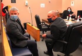 Kurt Churchill (left, in blue mask) sits in Provincial Court in St. John's with his lawyer, Robby Ash. Last year, Churchill was found guilty of threatening a police officer.