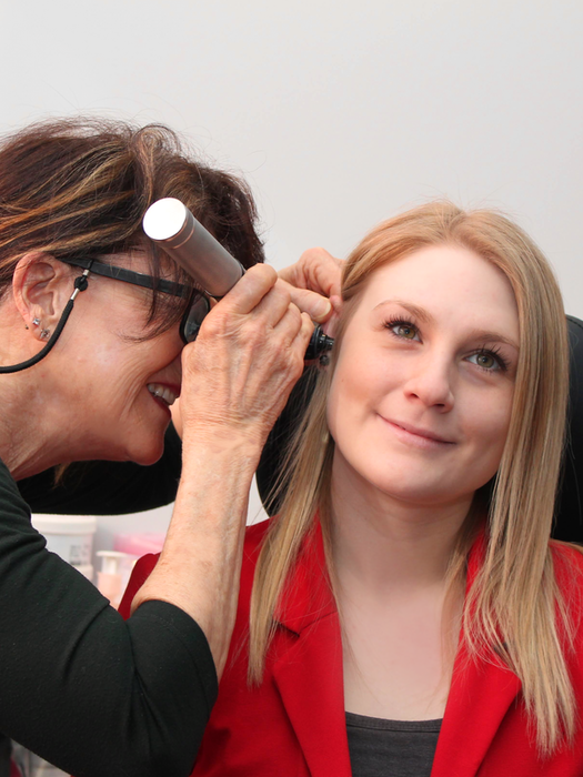 Audiologist, Devon Huning checking Patient Care Coordinator, Brittany Caravan's ear at the Corner Brook location.  - Photo Contributed.