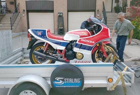 David Booth loads up his Honda motorcycle on Charles Snell's trailer. via David Booth