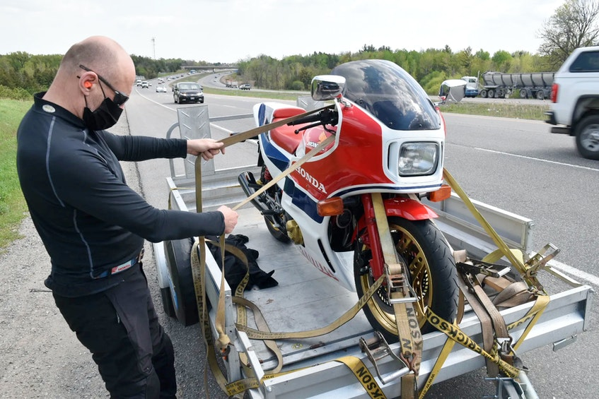 David Booth begins unloading his Honda motorcycle from Charles Snell's trailer.  via David Booth - POSTMEDIA