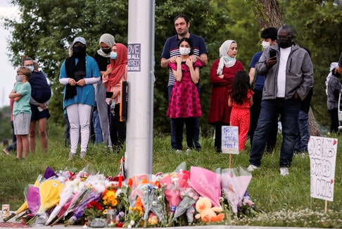 People gather at a makeshift memorial at the fatal crime scene where a man driving a pickup truck jumped the curb and ran over a Muslim family in what police say was a deliberately targeted anti-Islamic hate crime, in London, Ont., June 7, 2021.