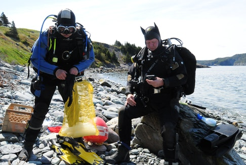 Scuba divers Katy MacPherson (left) and Doug Copp do their final checks before taking to their underwater at Admiral's Cove on Saturday morning.   -Joe Gibbons/The Telegram
