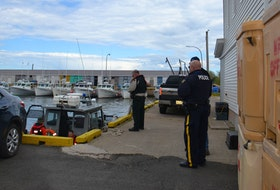 Police officers are shown at the wharf in Beach Point following a fatal fishing boat collision in 2018 that killed Chris Melanson and Justin MacKay.