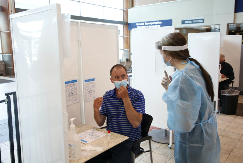 FOR PEDDLE STORY: Health staff member gives some instructions to an air passenger before they were to conduct their self-administered throat swab test in the arrivals area at Halifax Stanfield Airport Tuesday Jun8, 2021.   TIM KROCHAK PHOTO