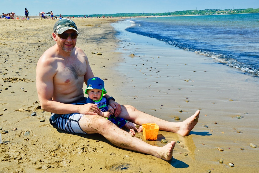 On what will probably be one of the hottest days this spring or summer, heading to the beach was a good idea. Michael MacNeil of Sydney kept a close watch on one-year-old Gabriel MacNeil while he played in the sand at Dominion Beach during Tuesday's 31 C-plus temperatures. ELIZABETH PATTERSON • CAPE BRETON POST