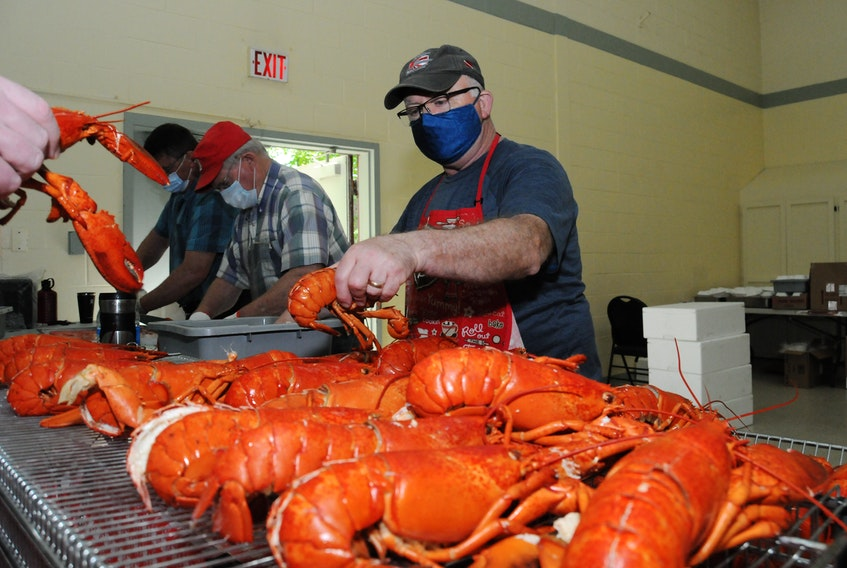 Volunteer Joe Earles places a split lobster into the pile to be packaged into a box for the takeout meals. -Joe Gibbons/The Telegram