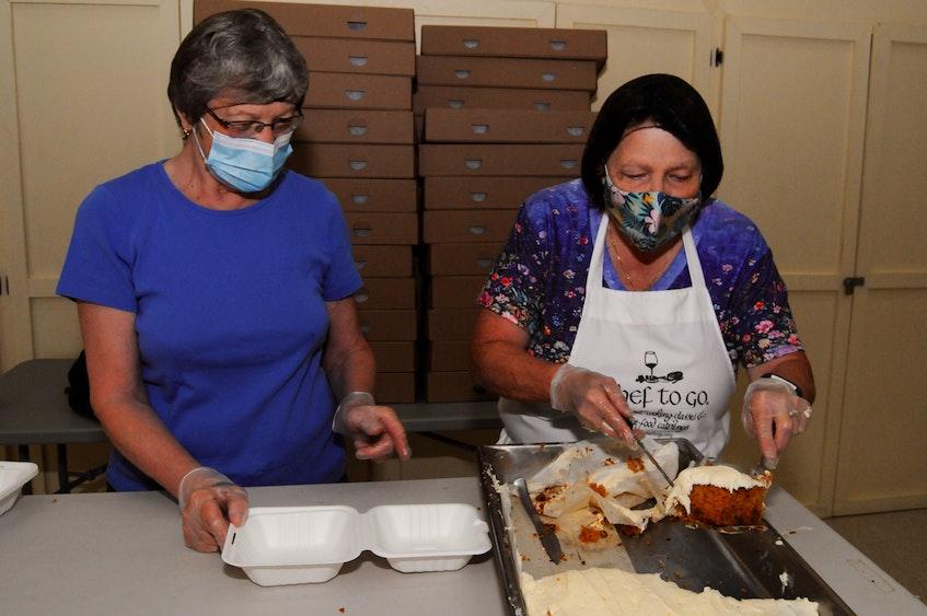 Carolyn Halliday (left) and Margaret Butt prepare carrot cake dessert slices. — Joe Gibbons/The Telegram
