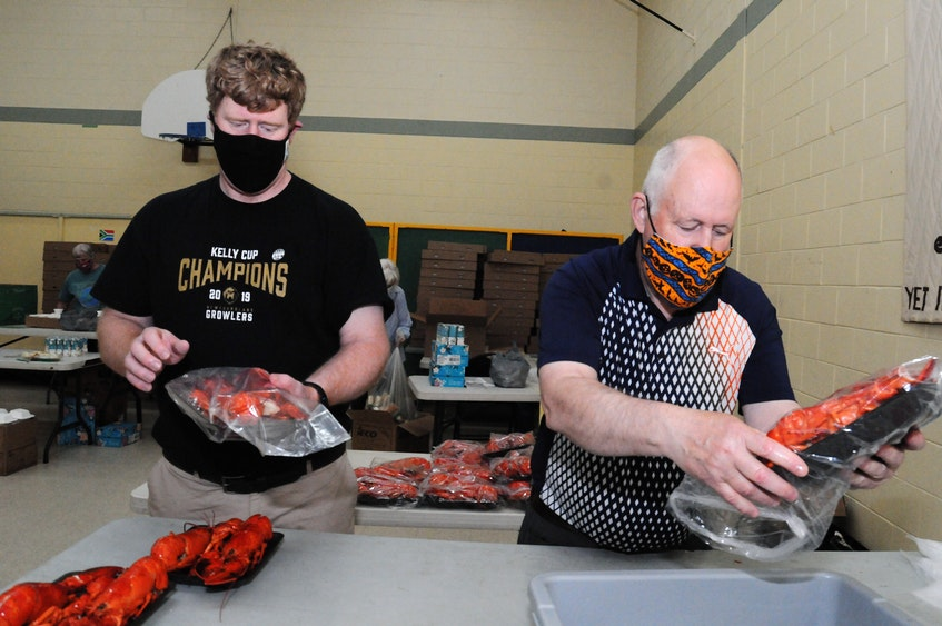 Draining lobsters, then packaging them on trays, are volunteers Tom Jackman (left) and Bill Eaton. — Joe Gibbons/The Telegram